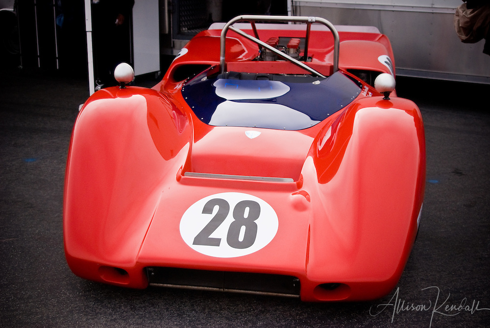 A red vintage racing automobile in the paddock between races at Laguna Seca during Monterey Car Week