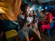 04 OCTOBER 2016 - BANGKOK, THAILAND: The daughter of a Chinese opera performer eats a snack beneath the stage while the performers put their makeup on at the Vegetarian Festival at the Chit Sia Ma Chinese shrine in Bangkok. The Vegetarian Festival is celebrated throughout Thailand. It is the Thai version of the The Nine Emperor Gods Festival, a nine-day Taoist celebration beginning on the eve of 9th lunar month of the Chinese calendar. During a period of nine days, those who are participating in the festival dress all in white and abstain from eating meat, poultry, seafood, and dairy products. Vendors and proprietors of restaurants indicate that vegetarian food is for sale by putting a yellow flag out with Thai characters for meatless written on it in red.     PHOTO BY JACK KURTZ