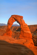 Delicate Arch, reddened by the setting sun, frames the La Sal Mountains near Moab, Utah. Delicate Arch is a 65-foot-tall (20 meters) freestanding natural arch located in Arches National Park. Delicate Arch is comprised of Entrada Sandstone and formed the same way other arches formed in the national park. It began as a sandstone fin, which was gradually worn away by weathering and erosion, leaving the arch behind.
