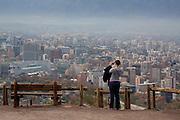 A woman take a picture of Las Condes and Providencia Neighborhoods in Santiago's metropolitan park.<br /> Parque metropolitano de Santiago, area verde mas importante de la capital.                      Santiago, Chile, Mayo de 2012.             Patricio Valenzuela Hohmann.