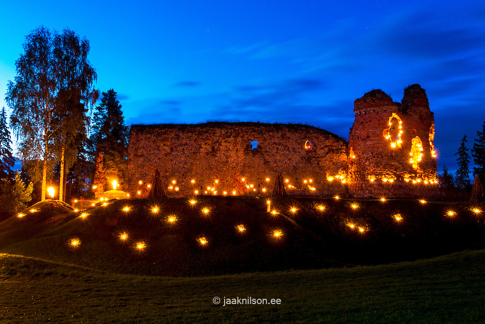 Vastseliina Bishop Castle Ruins in night with burning torches, Estonia