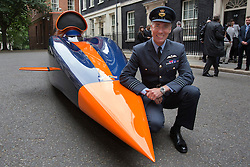 © licensed to London News Pictures. London, UK 24/06/2013. Captain Andy Green posing next to a replica of 13-metre long jet-and-rocket propelled Super Sonic Car on Downing Street, the car aims to beat the current land speed record of 763mph in 2014 and also to be the first land vehicle to exceed 1,000mph by 2015. Prime Minister is to announce a new apprenticeship initiative to create 100,000 Engineering Technicians. Photo credit: Tolga Akmen/LNP
