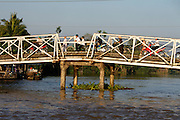 Mekong Delta. Motorbikes on a bridge across a river arm.