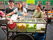 11 JULY 2011 - BANGKOK, THAILAND:  A fruit vendor serves a customer from her pushcart on a platform in Hua Lamphong train station in Bangkok. Hua Lamphong Grand Central Railway Station, officially known as the Bangkok Grand Central Terminal Railway Station, is the main railway station in Bangkok, Thailand. It is located in the center of the city in Pathum Wan District, and is operated by the State Railway of Thailand. The station was opened on 25 June 1916, after six years' construction. The station was built in an Italian Neo-Renaissance style, with decorated wooden roofs and stained glass windows. The architecture is attributed to Turin-born Mario Tamagno, who, with countryman Annibale Rigotti made a mark on early 20th century public building in Bangkok. The pair also designed Bang Khun Prom Palace (1906), Ananda Samakhom Throne Hall in The Royal Plaza (1907-15) and Suan Kularb Residential Hall and Throne Hall in Dusit Garden, among other buildings..There are 14 platforms and 26 ticket booths. Hua Lamphong serves over 130 trains and approximately 60,000 passengers each day. Thailand has the most advanced rail system in Southeast Asia and trains from Hua Lamphong serve all corners of the Kingdom.       PHOTO BY JACK KURTZ