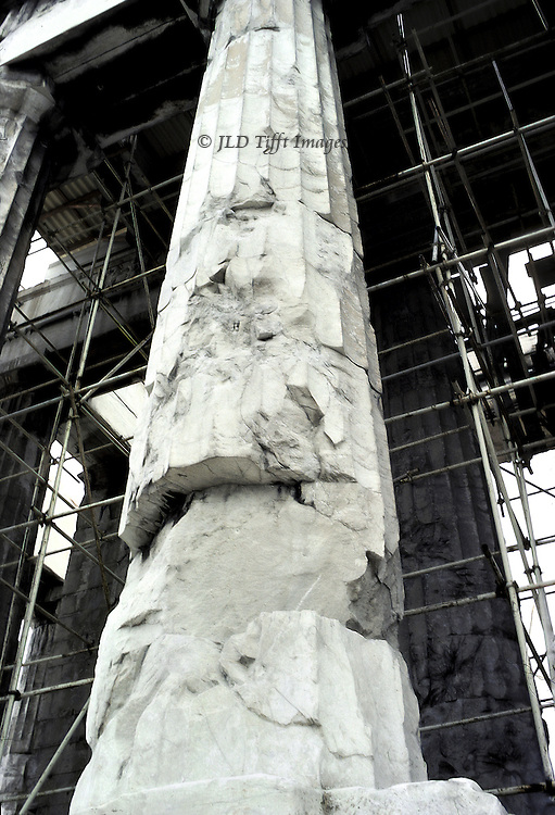 Acropolis, Parthenon: detail of a damaged column of the peristyle.  One vast gouge out of the column shaft.  Scaffolding visible beyond, around the cella..
