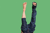 Low section of upside down man wearing jeans over colored background