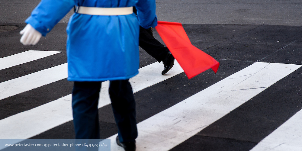 Official with red flag, on pedestrian crossing, Osaka, Japan.