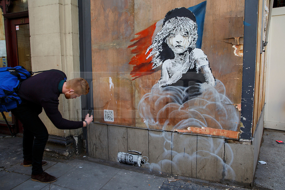 © Licensed to London News Pictures. 25/01/2016. London, UK. Members of public scanning a QR code of a new Banksy mural criticising the use of teargas on refugees in Calais has appeared on a building opposite the French Embassy in London on Monday, 25 January 2016. Photo credit: Tolga Akmen/LNP
