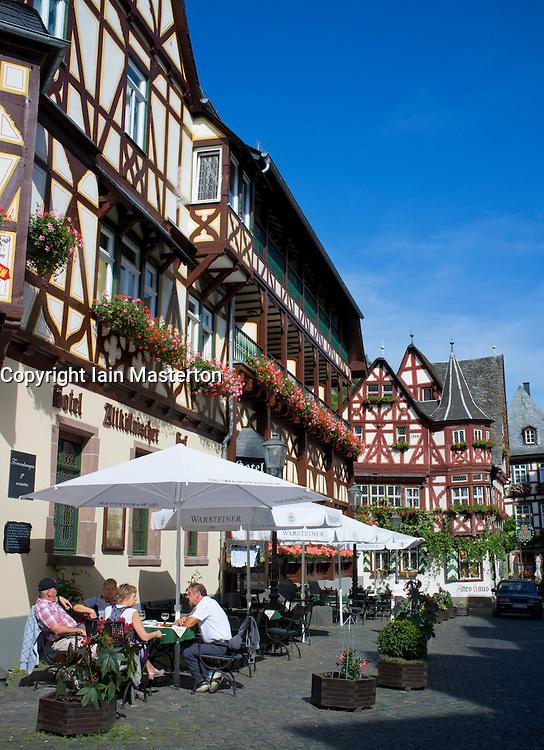 Bar on street beside historic buildings in Bacharach in Rhineland beside River Rhine Germany
