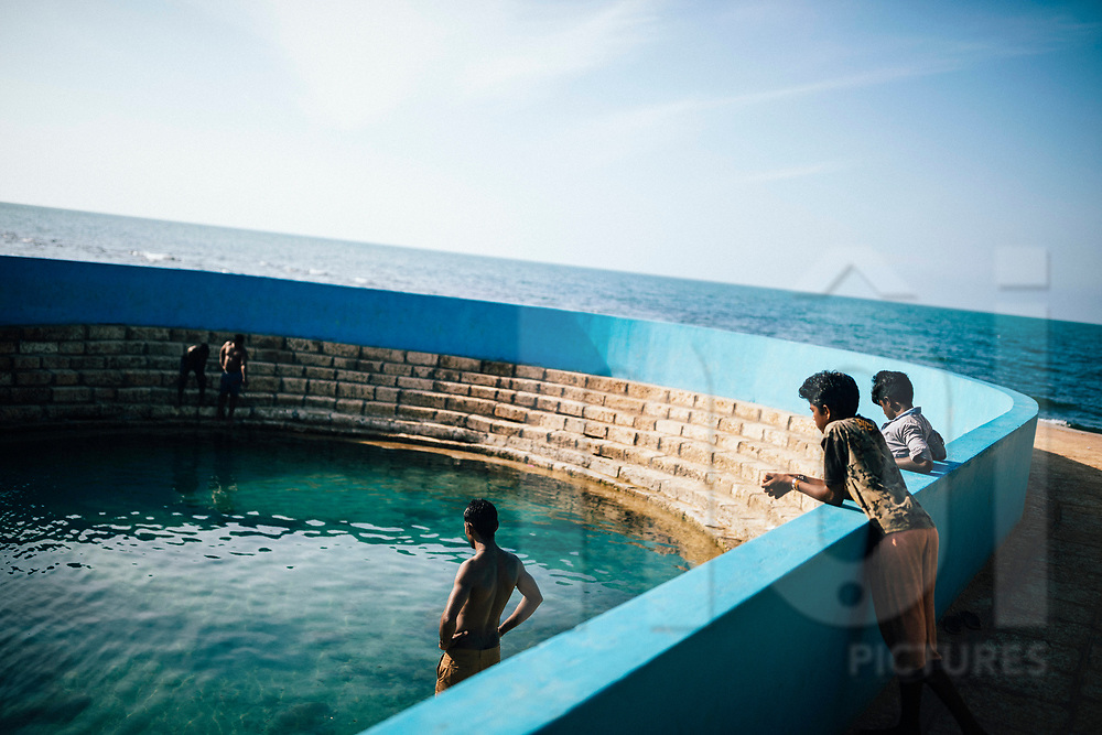Young men chills at the Keerimalai Springs, sacred pools fed by sea waters on the northern shores of the Jaffna Peninsula, Sri Lanka, Asia
