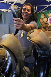 Olympia, London, August 9th 2015. Hundreds of real ale lovers attend the Campaign for Real Ale  Great British Beer Festival at London's Olympia Exhibition Centre, where dozens of independent breweries demonstrate the diversity of British brewed beers. PICTURED: A woman offers Viking drinking horns for sale.