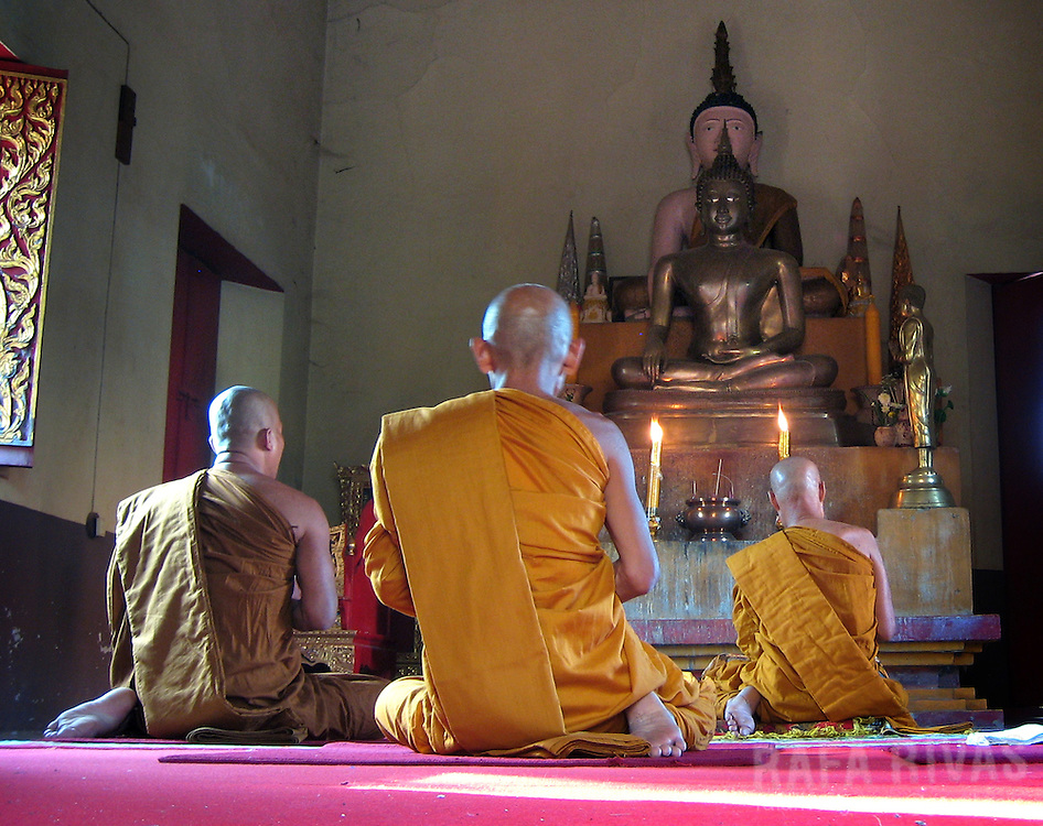 Buddhist monks pray at a temple in Ban Chiang, Thailand.