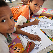 Boys spending their afternoon with Alola. Children are usually not allowed to act on their own but here the boys can give their crocodiles any colour they like. The Alola Foundation provide pre-school play and learn sessions. Education in Timor-Leste is very basic with classes up to 80 children and teachers trained under an old fashined system with very little inter-action between teacher and pupils..Fundasaun Alola is a not for profit non government organization operating in Timor Leste to improve the lives of women and children. Founded in 2001 by the then First Lady, Ms Kirsty Sword Gusmao, the organization seeks to nurture women leaders and advocate for the rights of women.