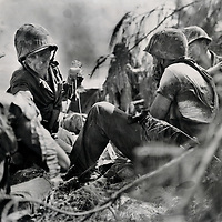 Navy Corpsman Bartolocci, attached to a Marine unit on Saipan, administers blood plasma to a wounded Marine while another, right, awaits his turn for treatmenet. This photo was made during  the fighting at the front lines.