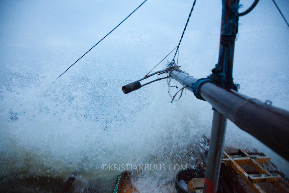 Breaking the waves on the way out to sea. Joseph is out front hanging on with both hands. <br /> <br /> Joseph is 17 and works like his father did on the sea as a fisherman. The catch of the day is hauled in by the entire crew to be sorted out on deck and taken straight to the market in Hinigaran. The catch that day made the crew $12.00 each( Captain Joan $24.00) One day a week Joseph goes to Alternative Learning schooling provided by Quidan-Kaisahan.  Quidan-Kaisahan is a charity working in Negros Occidental in the Philippines. Their aim is to keep children out of work to secure them education.