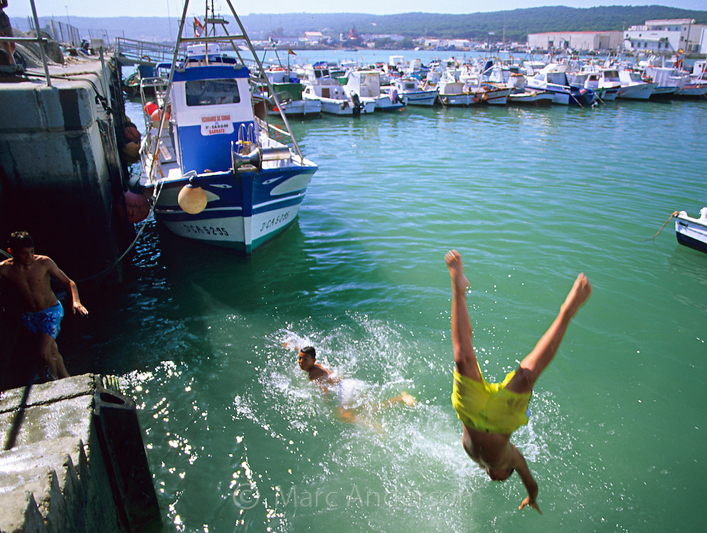 Boys diving into harbour, Barbate,  Costa de la Luz, Spain
