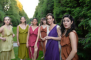 Old Westbury, New York, U.S. - June 21, 2014 - Lori Belilove & The Isadora Duncan Dance Company is in the South Allee, a sweeping walkway flanked by evergreens, shortly before the modern dancers will perform their finale of Midsummer Night event at the Long Island Gold Coast estate of Old Westbury Gardens on the first day of summer, the summer solstice. Ms. Belilove is wearing a white tunic with purple over-scarf.