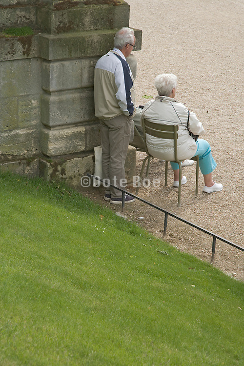 senior couple standing and sitting