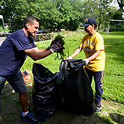 BRONX, NY - 8/18/2018 - Chief Machinists Mate <br /> Fred Delacuadra throws a handful of weeds into a bag held by Chief Select Hospital Corpsman Marchant Da Silva.  U.S. Navy Chief Selects from Navy Operational Support Center New York volunteered at Samuel H. Young American Legion Post 620 on Saturday as part of CPO365 Phase II.  (U.S. Navy Photo by Chief  Mass Communication Specialist Roger S. Duncan / RELEASED )
