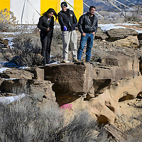 123014       Cable Hoover<br /> <br /> McKinley County sheriff's investigator Merle Bates, center, points to a dead body at the bottom of a cliff near U.S. Highway 491 north of Gallup Tuesday.
