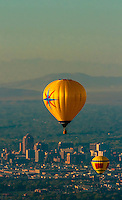 Aerial view, hot air balloons flying during the Albuquerque International Balloon Fiesta (with downtown Albuquerque in background), Albuquerque, New Mexico USA.