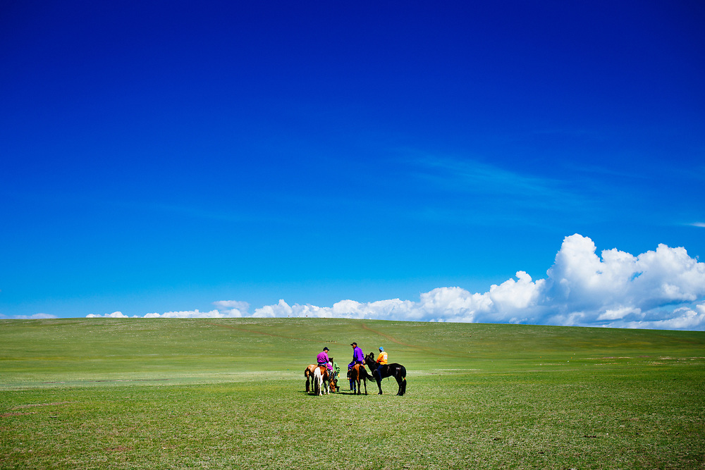 Horse riders against an open landscape during the traditional Naadam festival in Tsagaannuur, northern Mongolia.