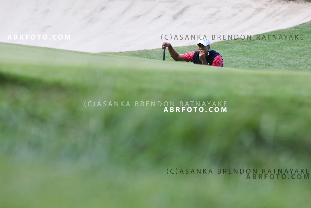 20 November 2011 : Tiger Woods crouches in front of the bunker to read the green ahead of his putt during the fifth-round Sunday Final round single ball matches at the Presidents Cup at the Royal Melbourne Golf Club in Melbourne, Australia. .