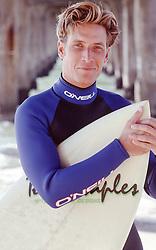 handsome blond surfer under a pier