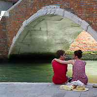 A couple rests in the shade of a bridge on the day the Italian Government and Heath Ministry has issued several warning for the current heath wave