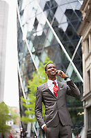 Happy African American businessman using cell phone outside building