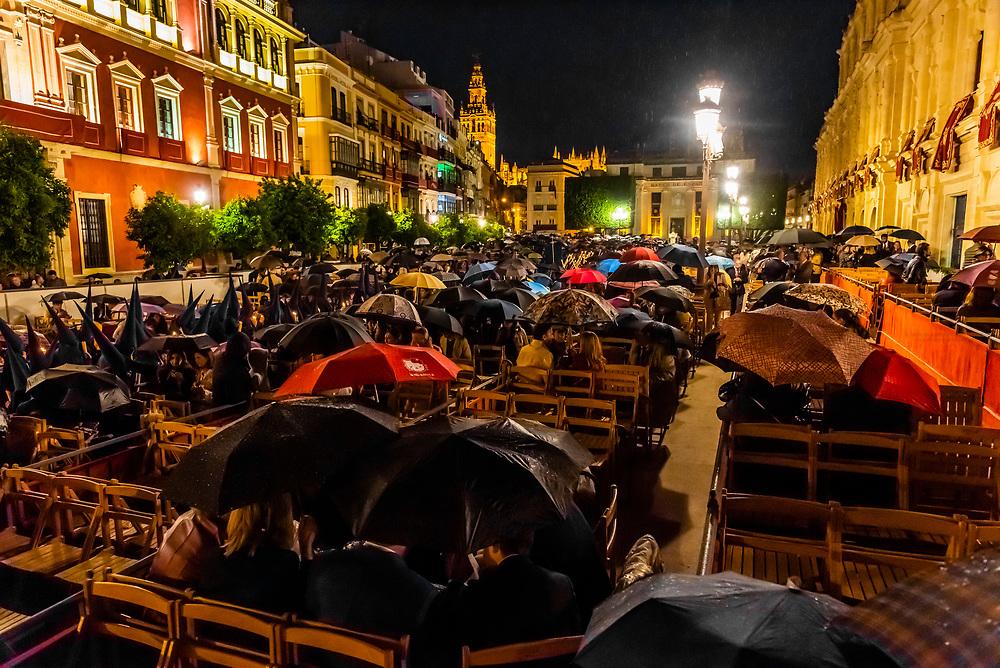 People watching Holy Week (Semana Santa) processions pass through Plaza de San Francisco, along the Official Path (Carrera Official), as light rain falls, Seville, Andalusia, Spain.