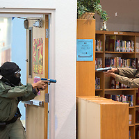 Officers with the Navajo Nation Police Department engage one of the two the mock shooters, Officer Sam Wood from the Apache County Sheriff's Department, in the library of Window Rock High School Wednesday. This exercise gave emergency responders the opportunity to practice handling a situation such as a school shooting.