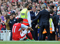 Football - 2016 / 2017 Premier League - Arsenal vs. Everton<br /> <br /> Everton Manager Ronald Koeman shakes the hand of Arsene Wenger as dejected Arsenal player Mesut Ozil sits on the ground after failing to qualify for the Champions League at the final whistle at The Emirates.<br /> <br /> COLORSPORT/ANDREW COWIE