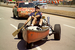 Stock photo of a man in scouts uniform riding in a row boat car