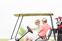 Happy woman looking at man while sitting in golf cart