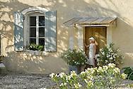 Woman in vintage dress standing at entrance,Le Domaine Saint Jean,St.Saturnin les Apt, Provence,France<br /> model release 0350
