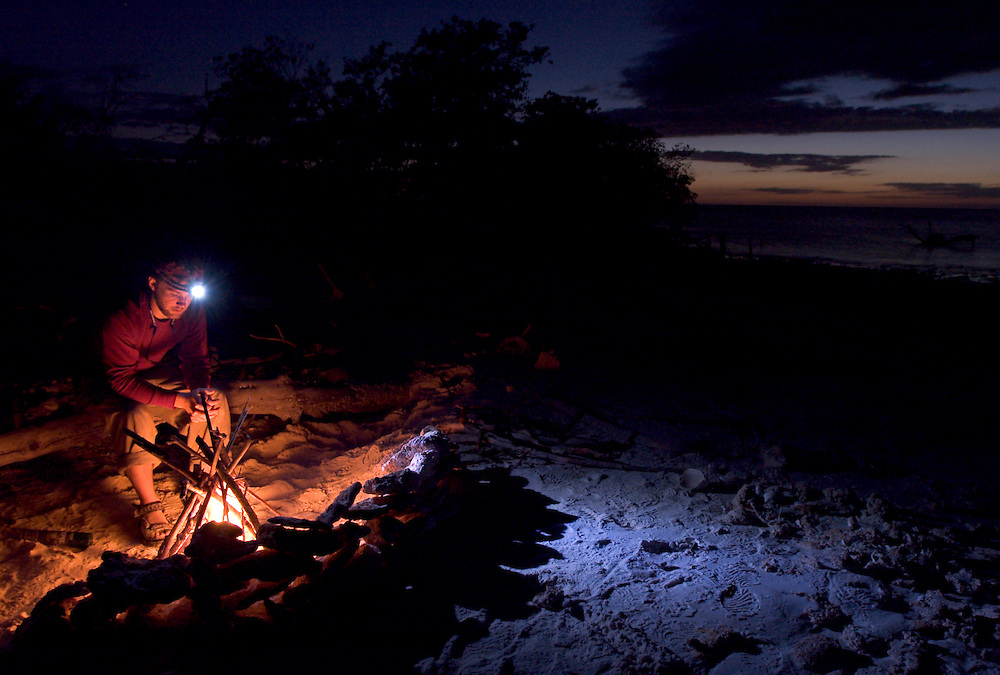 A backcountry camper warms himself by a campfire at his campsite on Round Key in the Everglades of South Florida.