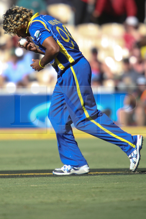 © Licensed to London News Pictures. 08/03/2012. Adelaide Oval, Australia. Lasith Malinga kisses the ball as he runs in to bowl during the One Day International cricket match final between Australia Vs Sri Lanka. Photo credit : Asanka Brendon Ratnayake/LNP