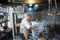 "MILANO, ITALY - 1 MARCH 2016: Mirko Savoldelli, an Italian inmate and cook, prepares a risotto for customers in the kitchen of the ""InGalera"" restaurant at the Bollate prison in Milan, Italy, on March 1st 2016.<br /> <br /> ""InGalera"" (which translates in English as ""InJail"") is the first restaurant located inside a prison and offering high-quality cooking to the public and a future to the inmates. It was inaugurated last October inside the Bollate prison in Milan. It is open five days a week for lunch and dinner, and seats 55 people. There are 9 people involved in the project, including cooks and waiters, all regularly employed and all inmates of the prison, apart from the chef and the maître d'hôtel, recruited from outside to guarantee the high quality of the food served. The restaurant is a project of the co-operative ABC La Sapienza - that operates inside the prison and provides more than 1,000 meals three times a day with the help of inmates they've hired - and of PwC, a multinational operating in the field of corporate consultancy. The goal of this project is to follow prisoners in rehabilitation process of social inclusion.<br /> <br /> The Bollate prison is already known for being a good example of penitentiary administration. The inmates are free to move around from one area to the other inside the prison (their cells open at 7:30am and close at 9pm) to go study, exercise in a gym, or work (in a call center, as scenographers, tailors, gardeners, cooks, typographers, among others)  in one of the 11 co-operatives inside the prison or in one of the private partnering businesses outside the prison. The turnover of the co-operatives that work inside the prison was €2mln in 2012."