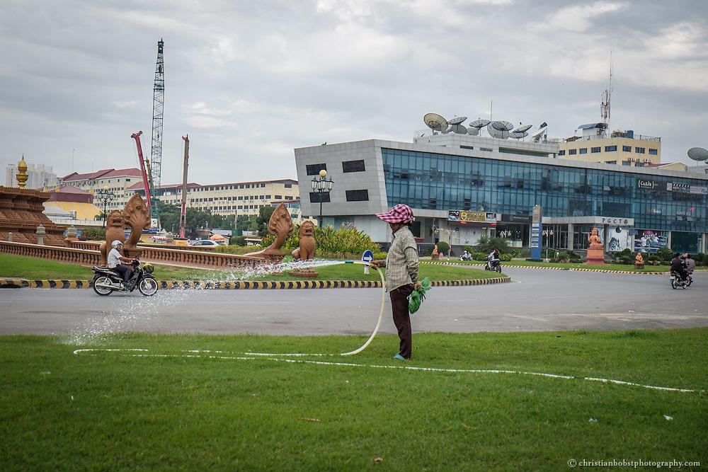 Eine Arbeiterin giesst den Rasen eines Kreisverkehrs vor dem Phnom Penh Daegu Gyeyong Buk Culture Tourism & Trade Promotion Centers, kurz PGCT Center genannt.