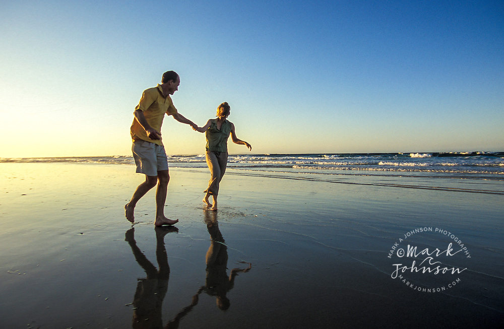 Couple on beach at sunset, Queensland, N. Stradbroke Island, Australia