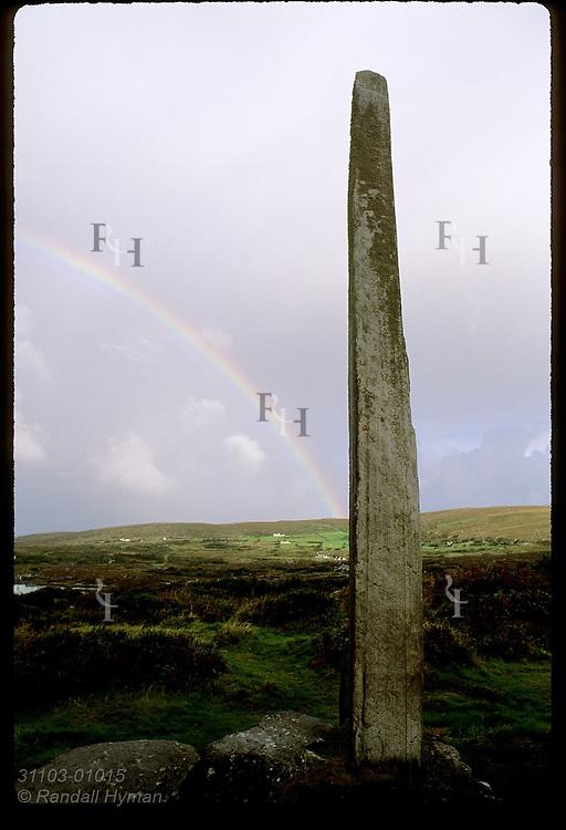 Rainbow intersects 5.3-meter-tall ogham stone, tallest in world, at Ballycrovane on the Beara Peninsula, Ireland.