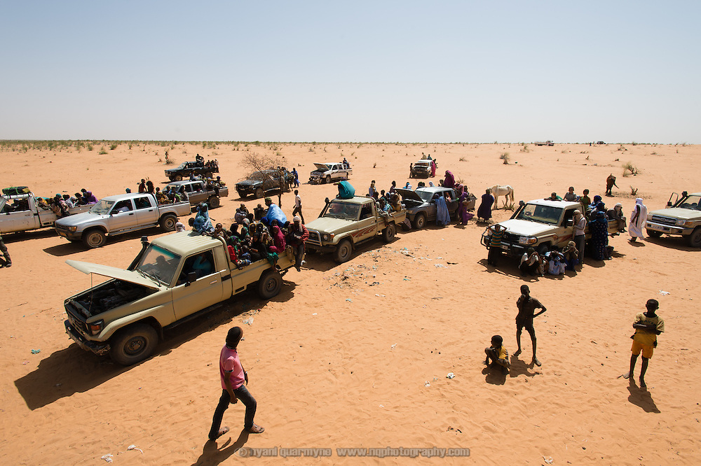 Pick-ups, each loaded with up to 30 Malian refugees and their meagre belongings, stand parked in the heat on the edge of the Mbera refugee camp in Mauritania while they wait for the rest of their convoy to catch up, on 6 March 2013. Many of the vehicles stand with the hoods open to allow the engines a chance to cool in the extreme heat. According to local NGO, ALPD, 825 refugees arrived in this convoy, packed into three trucks and an assortment of four wheel drive pick-ups.