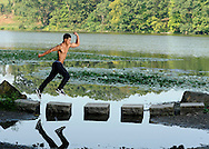 Benny Elzweig  models his muscles in front of Sunset Lake in the Rockefeller Preserve.