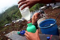 A worker hired by the Colombian government to manually eradicate coca crops washes in camp after a long day of work, in El Campanario, in a remote area of the southern Colombian state of Nariño, on Thursday, June 21, 2007. (Photo/Scott Dalton)
