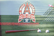 ANAHEIM, CA - JULY 26:  A bat and pair of baseballs lie on the grass in this double exposure photograph of a sign showing the years that the Angels were the AL West champs before the Los Angeles Angels of Anaheim game against the Detroit Tigers at Angel Stadium on Saturday, July 26, 2014 in Anaheim, California. The Angels won the game in a 4-0 shutout. (Photo by Paul Spinelli/MLB Photos via Getty Images)