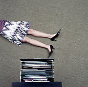 Woman lying on floor beside filing cabinet, low section, overhead view