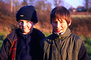 A3AAWD Two twelve year old boys standing shoulder to shoulder posing outdoors in winter
