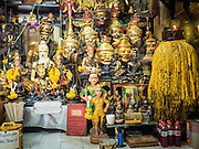 """25 MAY 2015 - BANGKOK, THAILAND: The shrine in Ajarn Neng Onnut's (also known as Khun Pean) Sak Yant tattoo parlor. Sak Yant (Thai for """"tattoos of mystical drawings"""" sak=tattoo, yantra=mystical drawing) tattoos are popular throughout Thailand, Cambodia, Laos and Myanmar. The tattoos are believed to impart magical powers to the people who have them. People get the tattoos to address specific needs. For example, a business person would get a tattoo to make his business successful, and a soldier would get a tattoo to help him in battle. The tattoos are blessed by monks or people who have magical powers. Ajarn Neng, a revered tattoo master in Bangkok, uses stainless steel needles to tattoo, other tattoo masters use bamboo needles. The tattoos are growing in popularity with tourists, but Thai religious leaders try to discourage tattoo masters from giving tourists tattoos for ornamental reasons.       PHOTO BY JACK KURTZ"""