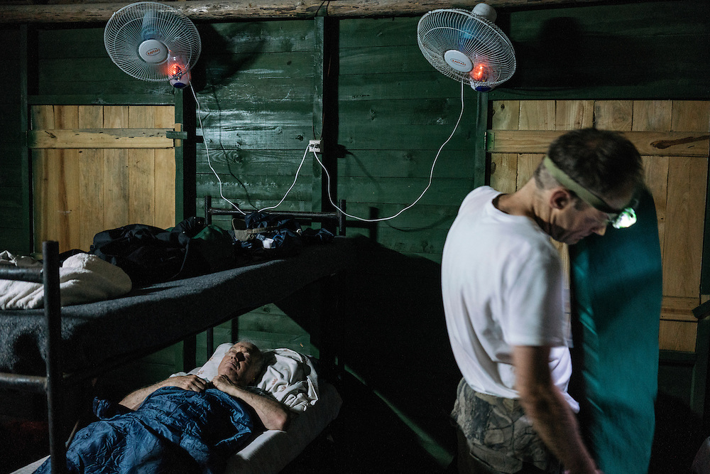 Ornithologist Tim Gallagher lies down while Martjan Lammertink readies his sleeping bag in a hut at Taco Bay, a tourist campsite on the coastline, while they waited for the permit to Humbolt National Park to be accepted on Jan. 26, 2016.